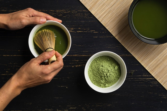 Matcha is whisked into water using a traditional whisk. Matcha, or powdered green tea, has a much higher caffeine content than leaf green tea or coffee.