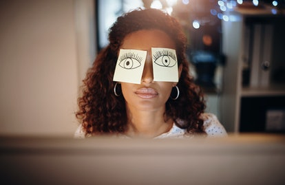 A woman has open eyes drawn on Post-Its on her eyes while she naps. The brain repairs itself while you sleep, and sleep deprivation interrupts several necessary processes for cognitive function.