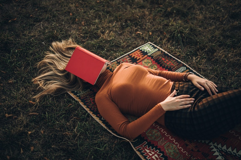 A woman sleeps under a book. The brain needs sleep to operate properly, and not just because it's tired.