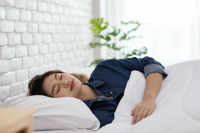 A woman sleeps. White noise has been shown to be helpful for sleep in some situations. However, researchers caution against using it as a long-term solution for sleep problems.