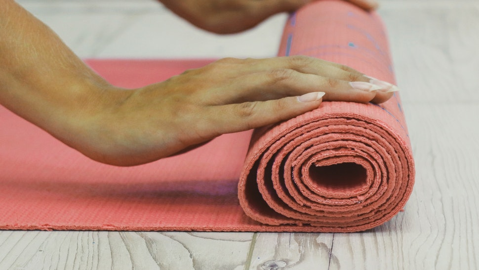 A person rolls up a yoga mat. Yoga poses can trigger gender dysphoria