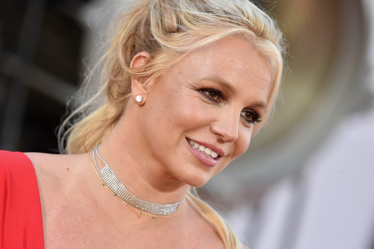 Britney spears smiles wearing a red dress, sparkly necklace, earrings and her hair in a ponytail.