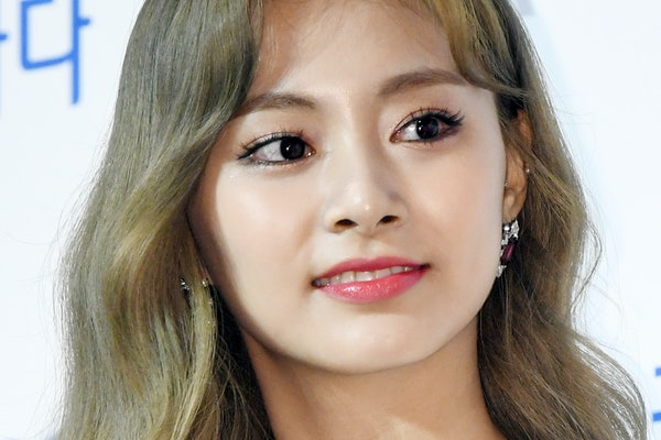Tzuyu steps out in a white dress for a red carpet event.