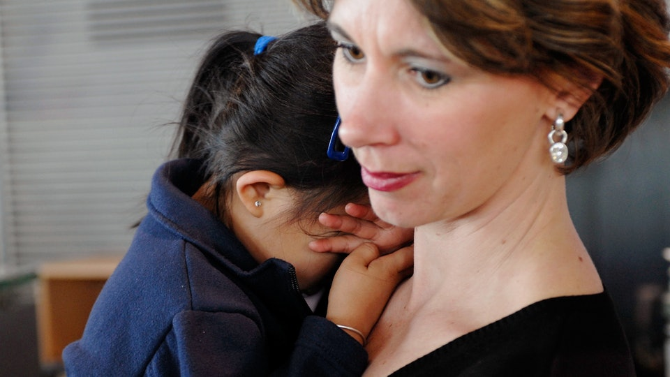 A picture of a woman holding a young toddler, crying on her shoulder.