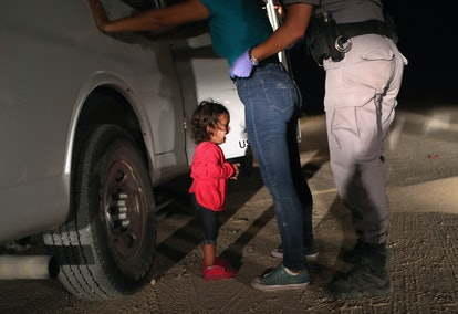 A picture of a young immigrant child, crying, while her parent is being searched by a border patrol ...