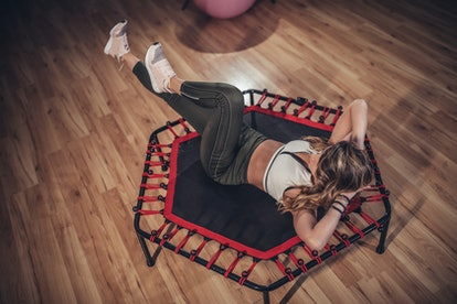 A woman does crunches on a trampoline, one of the questionable fitness trends of the '10s.