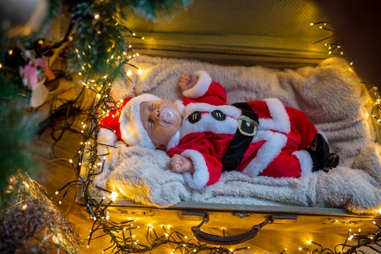 a newborn baby in a santa suit posed with Christmas lights
