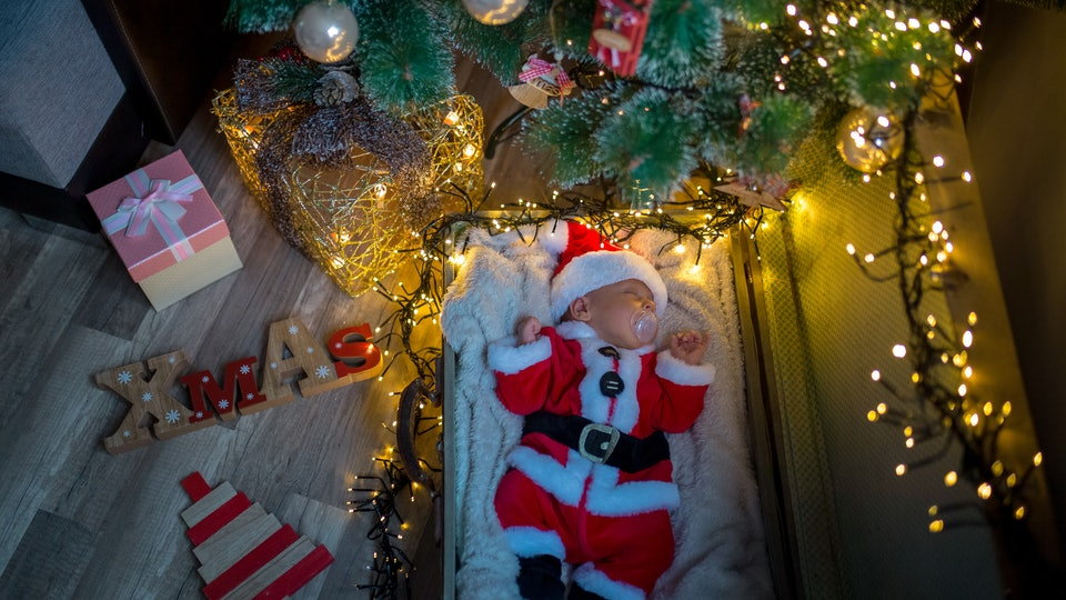a baby dressed in a santa suit under a Christmas tree
