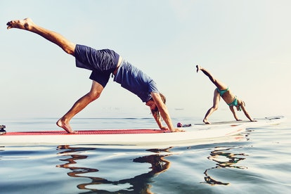 Two people doing paddleboard yoga. One of the fitness trends of the last decade was, funnily enough, paddleboard yoga.