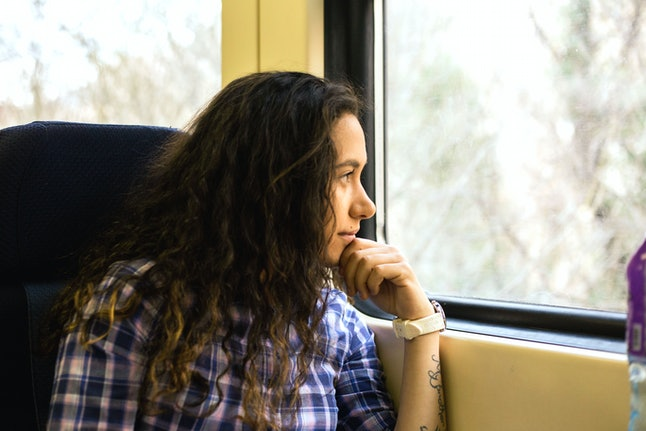 A woman staring out the window of a train, traveling home for the holidays. Nosy relatives are an inevitability at the holidays, so it's helpful to have a plan.
