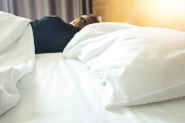 A woman lying on her side in bed. Loss of libido can be a  sign of low estrogen.