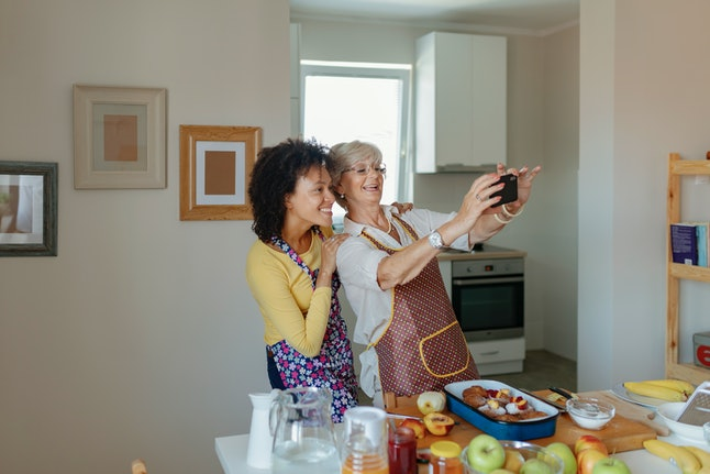 A daughter with her mother take a selfie while baking at the holidays. Redirecting is a great tactic to avoid nosy questions from family members.