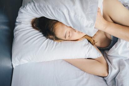 A woman sleeps in her bed. Depression can increase the likelihood of nightmares, and disturbed sleep...