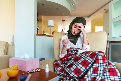 A person wrapped in a plaid blanket sits looking at a thermometer with tissues and oranges on the ta...