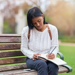 A woman on a bench writes her to-do list in a notebook so she can stop forgetting things.