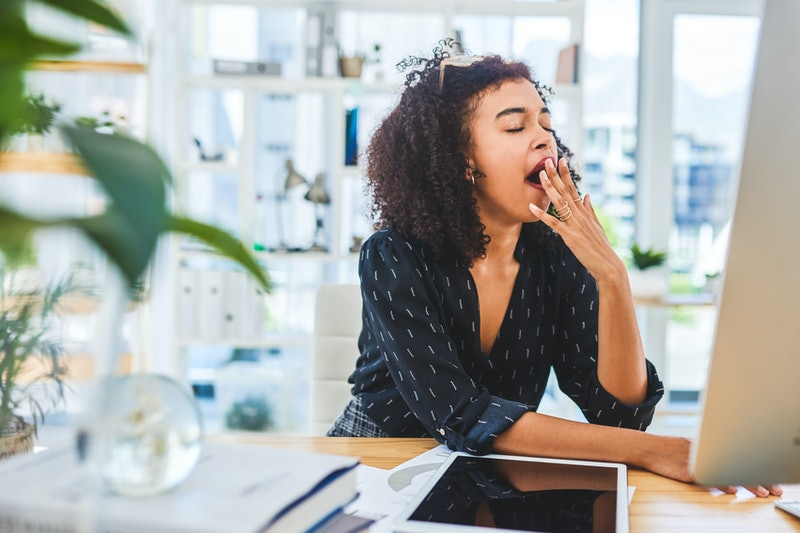 A woman yawns in front of her computer. Burnout affects your brain in key ways, an expert tells us.