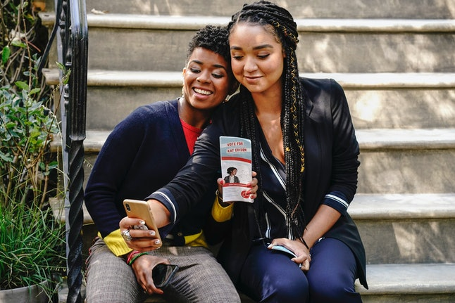 Kat and her campaign manager Tia sit on a porch while taking a selfie on the show The Bold Type. Queer people of color often do not have access to affirmative, safe, and effective reproductive health care, studies say.