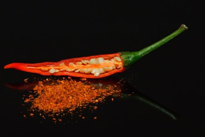 A chili pepper, cut in half long-ways against a black background, revealing fresh seeds inside and a smattering of crushed seeds in front of it. Eating chili peppers frequently can reduce your risk of dying from a heart attack, stroke, or cancer, studies suggest.
