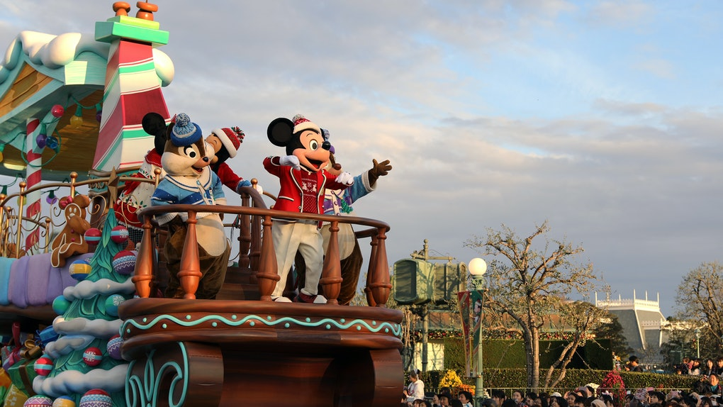 Mickey Mouse and other Disney characters pose on float in Magic Kingdom during a Christmas celebration.