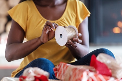 A woman wraps holiday presents. The holiday season goes so fast thanks to a variety of psychological factors.