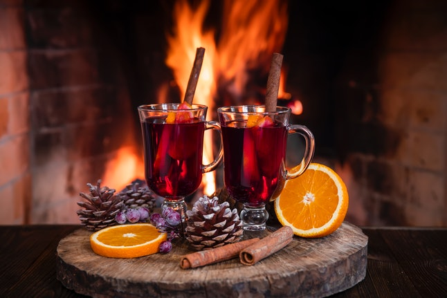 Two glass mugs with cinnamon sticks on them and next to them, along with grapes, orange slices, and pinecones on a table foreground against a fireplace. Cinnamon can help stabilize and regulate your blood sugar levels, expert says.