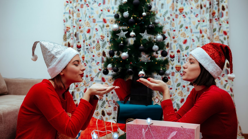 Two women wearing red sweaters and Santa hats smile and get ready to blow fake snow over their presents in the living room on Christmas.