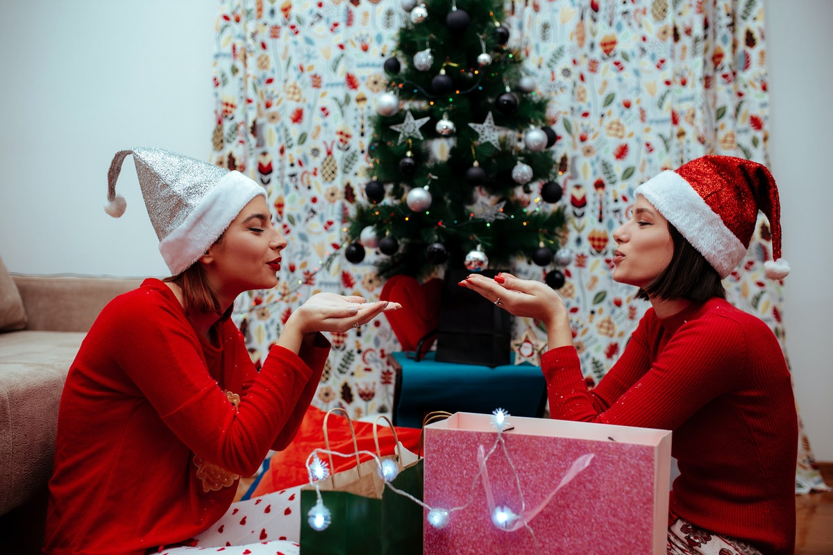 Two women wearing red sweaters and Santa hats smile and get ready to blow fake snow over their prese...