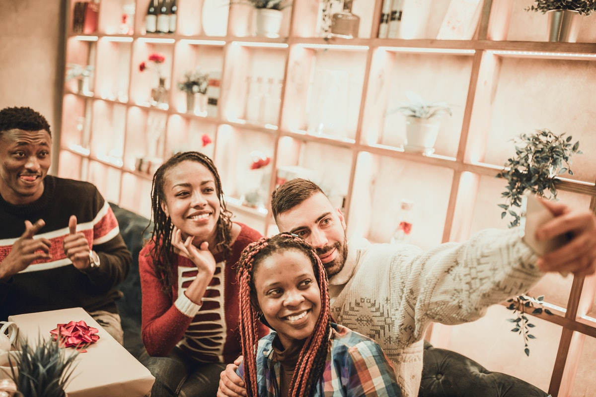 A group of friends takes a selfie while catching up at a restaurant over Christmas break.