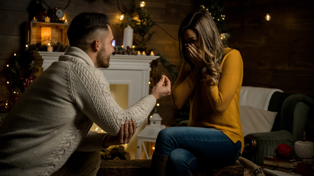 A guy proposes to his girlfriend in their family room on New Year's Eve.