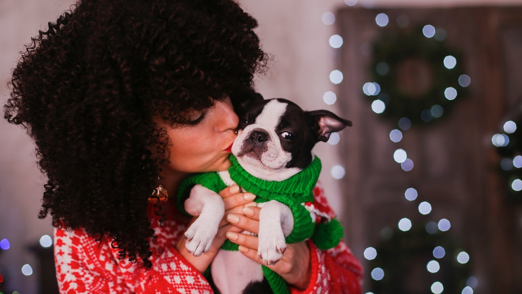A woman hugs and kisses her puppy wearing a festive sweater on Christmas morning.