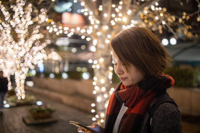A woman types on her phone in front of Christmas lights. A support network of family and friends can come to the rescue if you're struggling with body image during the holidays.