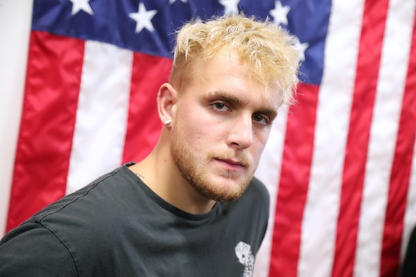 Jake Paul poses in front of an American Flag.