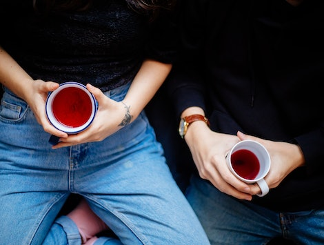 Two women hold herbal tea. Going sober for January is increasingly popular, and you may see small changes in your body in just one week.
