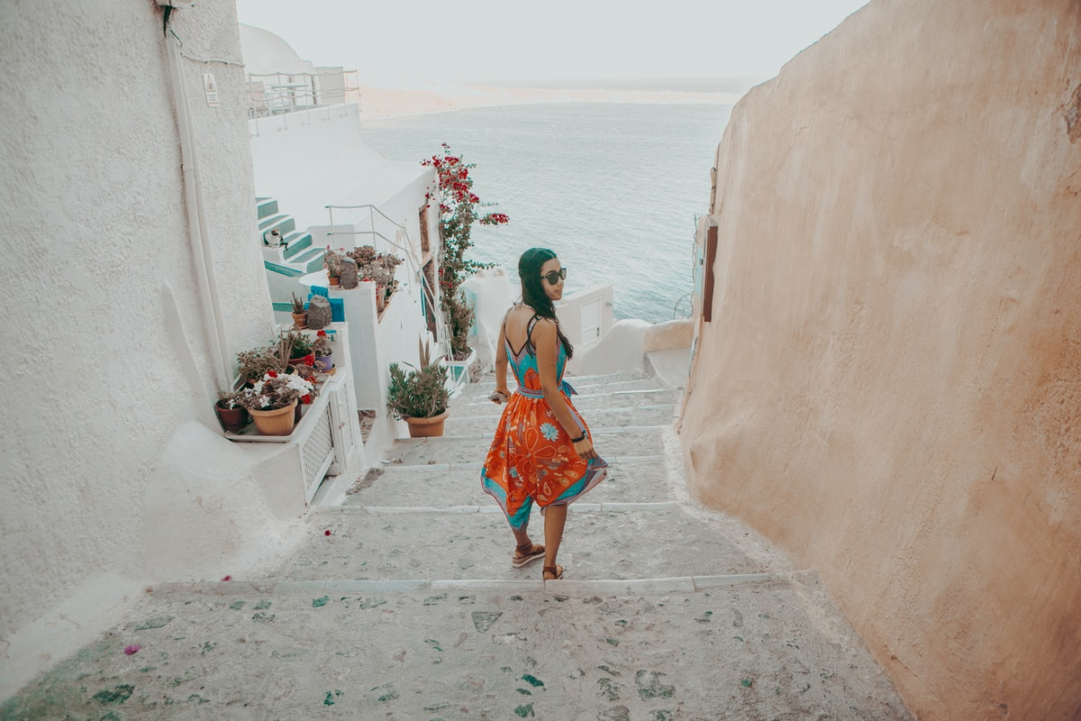 A woman walks down stairs toward the ocean while on an underrated family vacation in Santorini, Gree...