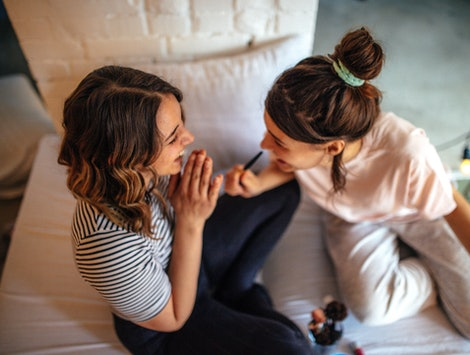 Two women in their pajamas do their makeup before a night of staying in.
