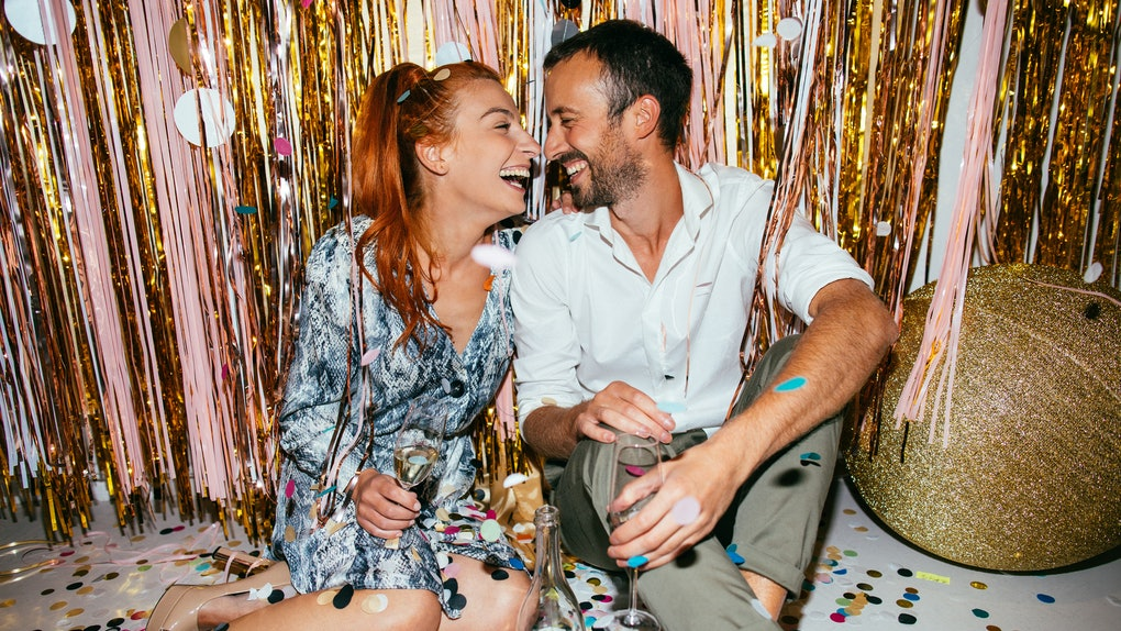 A couple sits on a floor covered with confetti on New Year's Eve as they toast their champagne flutes and laugh.