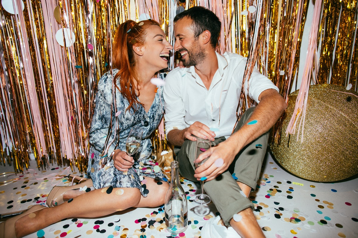 A couple sits on a floor covered with confetti on New Year's Eve as they toast their champagne flute...