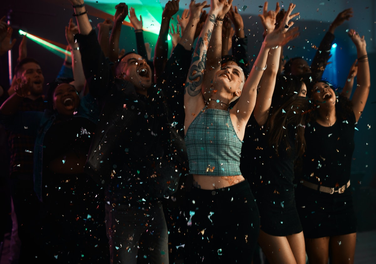 A group of friends throw up their arms at a club under confetti on New Year's Eve.