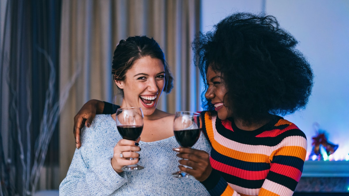 Two girl friends smile with their glasses of red wine at home for New Year's Eve.