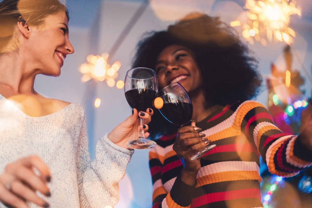 Two girl friends clink their wine glasses and hold sparklers on New Year's Eve.
