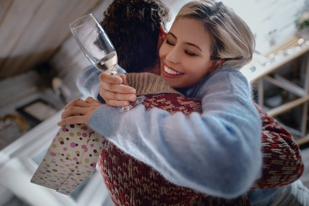 A blonde woman holding a glass of champagne hugs her boyfriend at home on New Year's Eve.