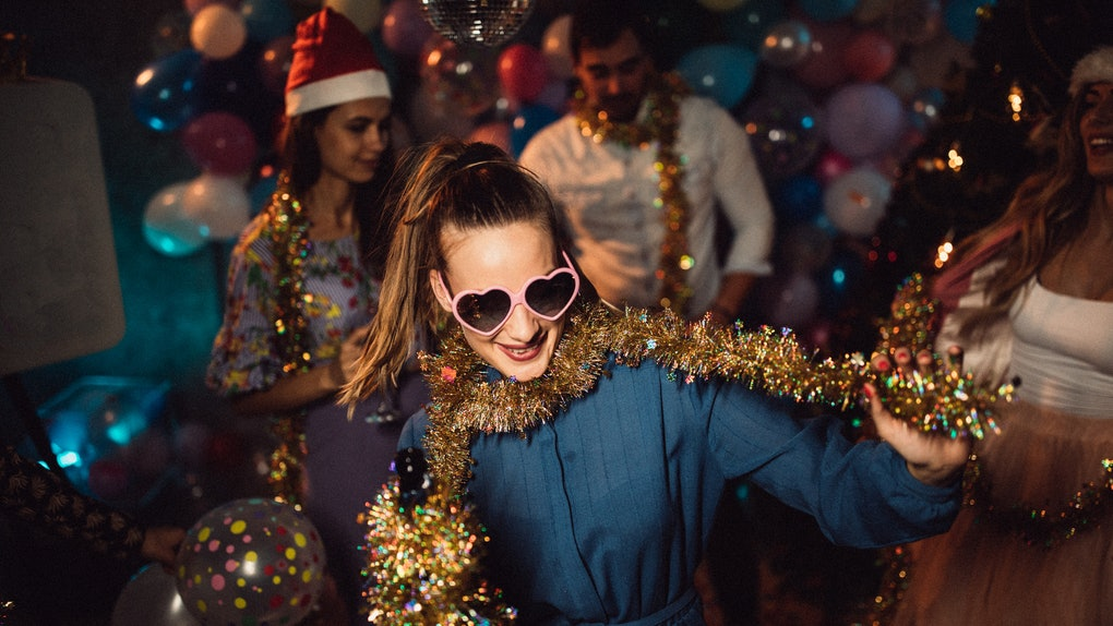 A girl wearing tinsel and heart-shaped sunglasses smiles and dances at a party on New Year's Eve.