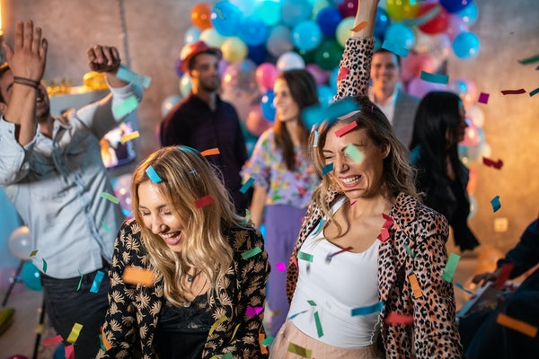 Two blonde girls smile and party while confetti falls from ceiling on New Year's Eve.