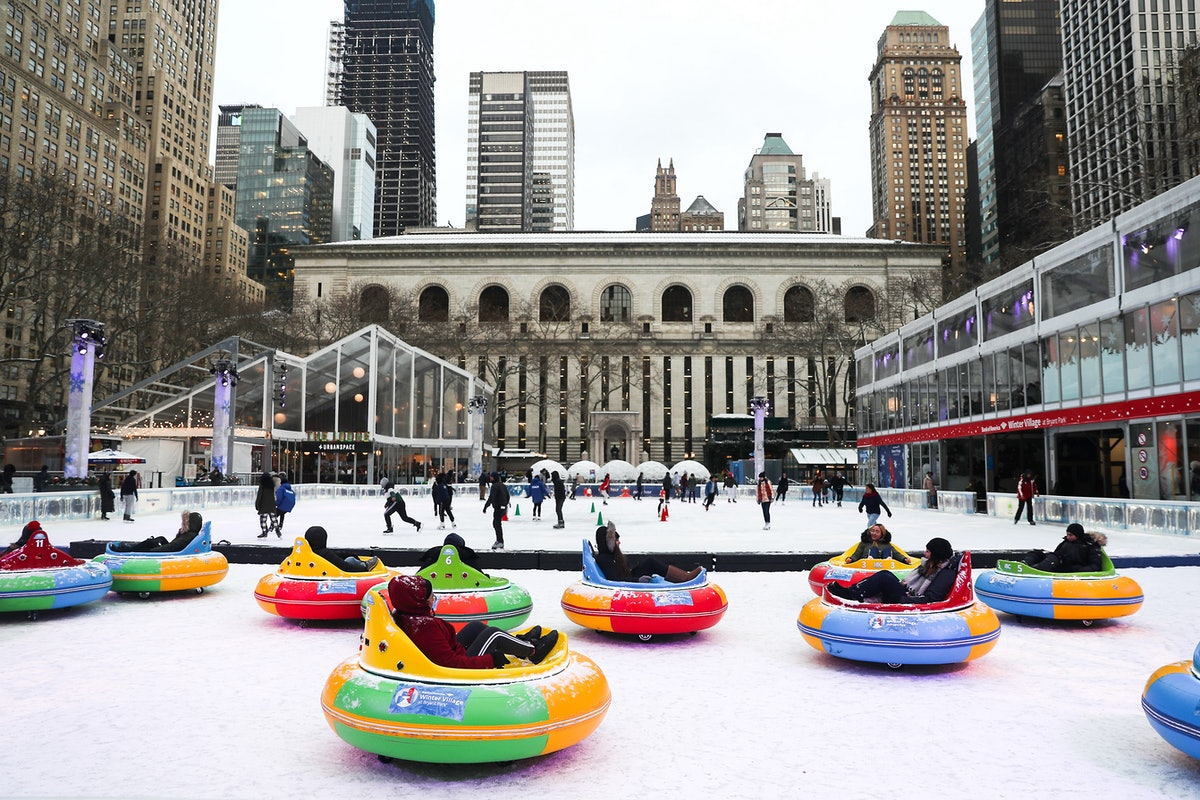 Travelers ride around in bumper cars on ice during FrostFest in Bryant Park in New York City.