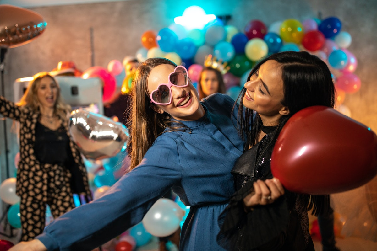 Two friends smile and party on New Year's Eve with balloons.