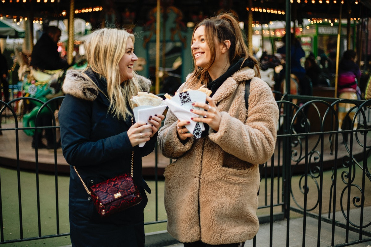 Two fashionable best friends pose in front of a carousel while holding snacks from Time Out Market N...