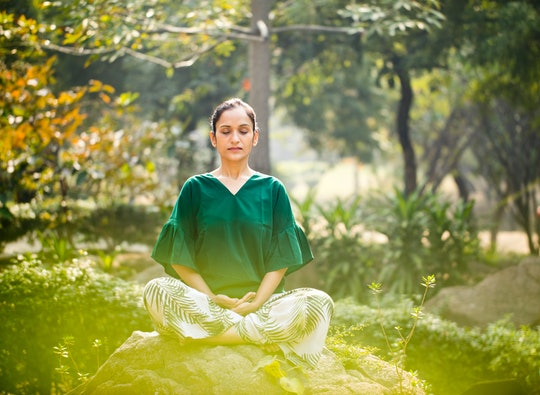 a woman sitting cross-legged on a rock meditating