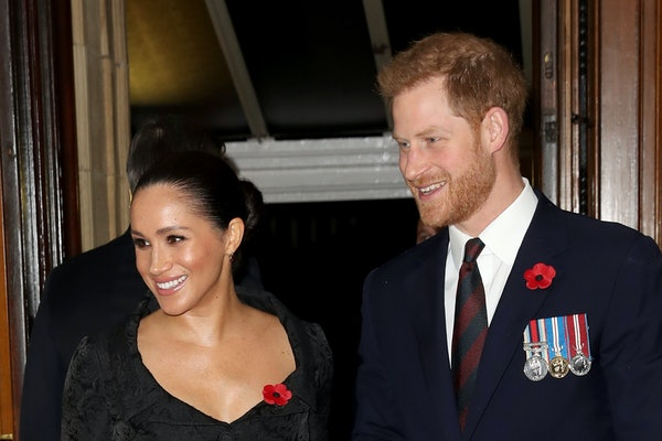 Meghan Markle and Prince Harry flash smiles for the camera.