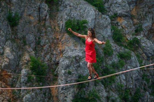 woman walking a tightrope in heels between cliffs