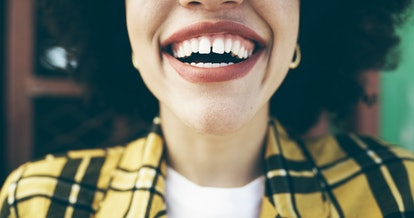 A person wearing a blue and yellow checked blazer smiles for the camera. Brushing your teeth at least 3 times a day was linked to a lower risk of heart failure